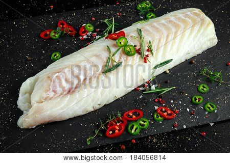 Fresh Raw Cod loin fillet with rosemary, chillies, cracked pepper on stone board.