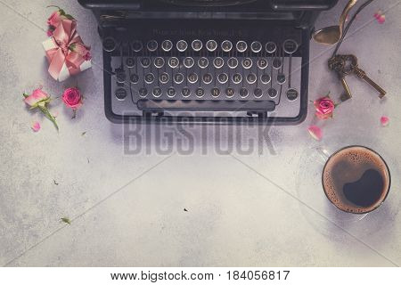 Workspace scene frame with vintage typewriter, coffee and keys, retro toned