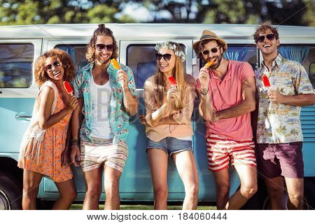 Group of friends having ice lolly in park