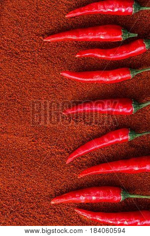 red hot chili peppers, popular spices concept - decorative pattern in the form of a steps of the staircase made of chili red hot pepper pods on a brown background of dried paprika, flat lay, vertical
