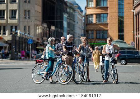 RIGA LATVIA - AUGUST 14 2015: Group of tourists on bicycles in the streets. Guided tour led by a guide.