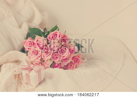 Female dress and jewellery with freah roses bouquet and gift box on chair with copy space, retro toned