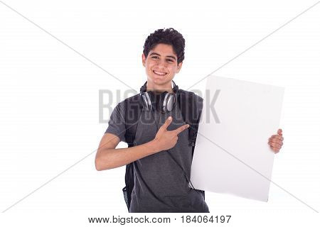 Smiley happy friendly young student holding an empty blank board and pointing to it teenager wearing gray t-shirt with a headphone and back-bag isolated on white background