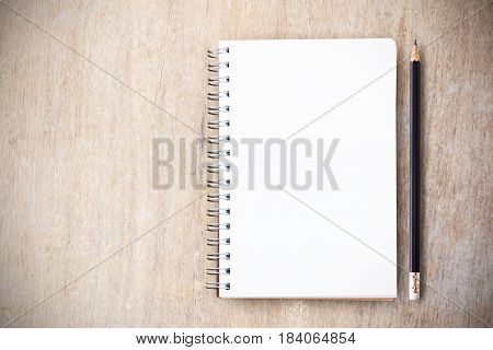 Note pad and black pencil on wood table top view with copy space for any design