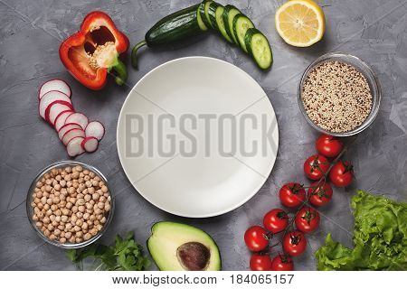Ingredients for a bowl buddha: quinoa chickpeas fresh vegetables on gray concrete background. View from above