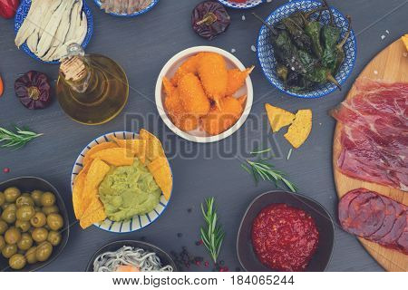 Table with spanish tapas - green peppers padron, jamon, croquetes, guacamole and olives, top view of picnic table, retro toned