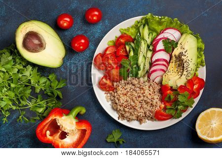 buddha bowl with mixture of vegetables quinoa on blue background