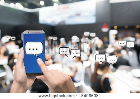 Hand holding mobile phone showing chat message when Live via social network over Abstract blurred photo of conference hall or seminar room with attendee background business technology concept.