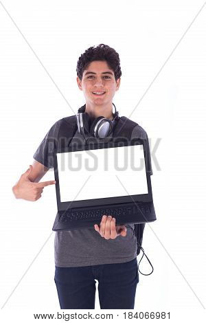 Portrait of smiley happy friendly young student holding a labtop and pointing to it teenager wearing gray t-shirt and jeans with a headphone and back-bag isolated on white background