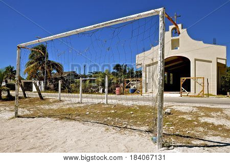 A worn out soccer net in a sandy field surrounded by litter and debris is located in a small Mexican village.