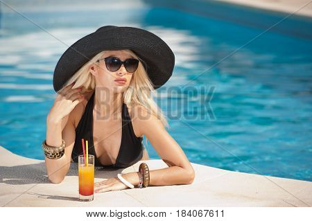 Beautiful sensual blonde with fashionable sunglasses relaxing in the pool with a juice. Attractive long hair woman in black low-cut swimsuit at swimming pool. young female, summer shot juice glass.