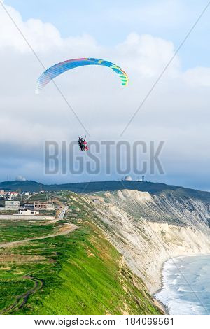 Flying tandem paragliders over the sea close to mountains, vertical view of the landscape.