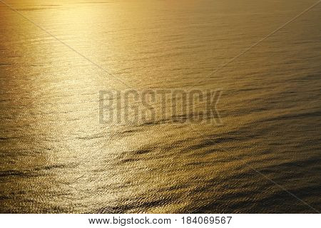 View on the waves sparkling in the golden light of the evening sun. Can be used as a background.