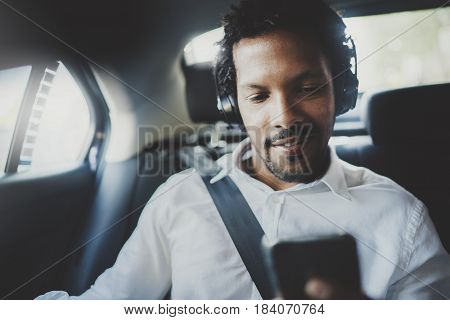 Young smiling african man using smartphone while sitting on backseat in taxi car.Concept of business people traveling.Blurred background
