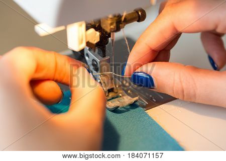 needlework and quilting in the workshop of a tailor - close-up on fingers of tailor female with blue manicure sticking thread in a needle of sewing machine
