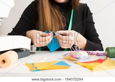 needlework and quilting in the workshop of a young woman - close up on hands of a tailor sews with a needle pieces, colorful fabrics on the desktop with threads, scraps of fabric and spin cushion