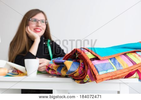 needlework and quilting in the workshop of a tailor - table with folded colorful patchwork fabrics during the lunch break of a tailor with a cup of tea