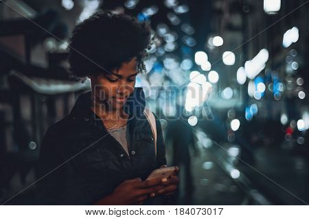 Beautiful pensive black Brazilian girl chatting on smartphone while standing on night street thoughtful female teenager with curly afro hair using her cell telephone in evening urban settings