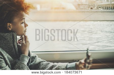 True tilt shift portrait of pensive black teenager girl using smartphone inside of ship cabin biracial young female with cell telephone near ship window with river water outside on moody day