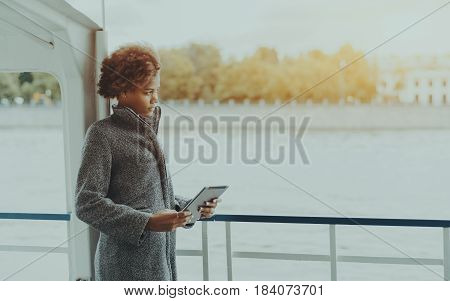 Attractive serious black girl is standing on the deck of a ship with digital tablet pensive biracial teenage female with curly afro hair holding touch pad while standing on seafront with copy space