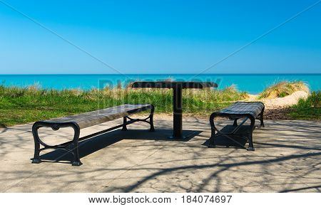 Benches and a table in a park on a lake