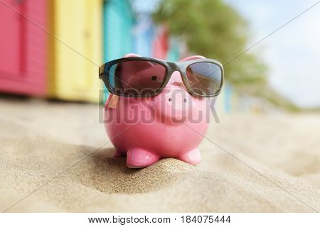 Piggy bank on sand beach vacation with sunglasses and bathing boxes