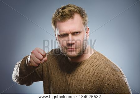 Portrait of angry man isolated on gray background. He raised his fist to strike.