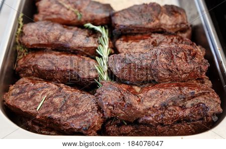 A lot of cooked veal steaks rib eye. On the steaks lies a branch of fresh rosemary