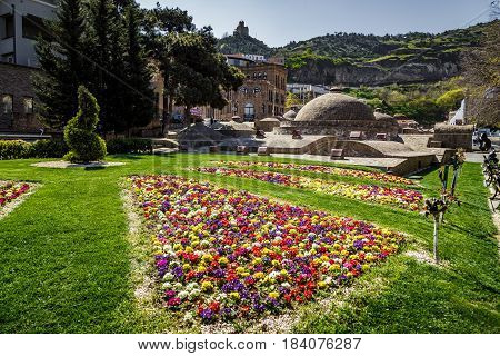View of the old sulfur baths in Tbilisi in the foreground a bright flower bed. April 17 2015