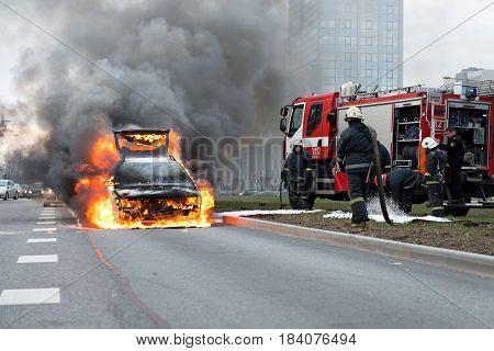 RIGA LATVIA - APRIL 11 2014: Out into the road burning car. There are just arrived firefighters. Preparing to fire extinguishing works. Traffic is stopped.
