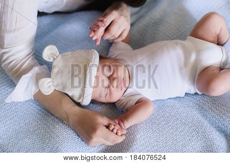 Newborn baby boy with mother. Baby sweet sleeping on a white bed.