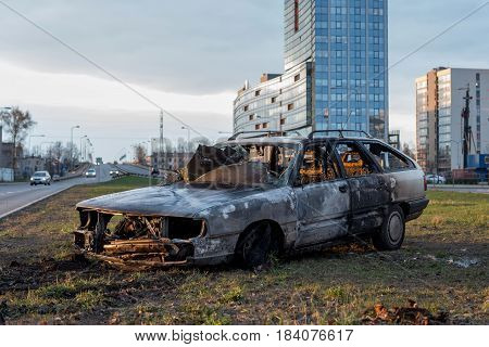 RIGA LATVIA - APRIL 11 2014: Burnt car harvested from the road. The traffic is restored.