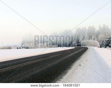 Winter landscape. Winter road in the morning mist.