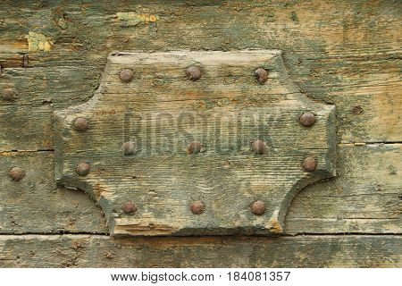 Old wooden decoration on an old wood door. Textured wood background close up