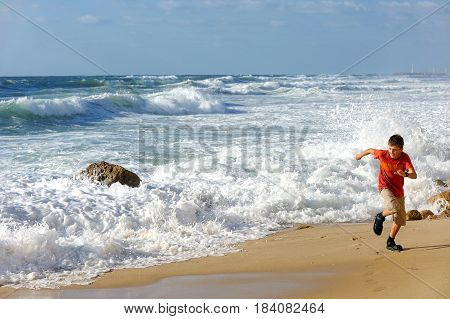 Boy runs along the shore of the Mediterranean Sea in Israel