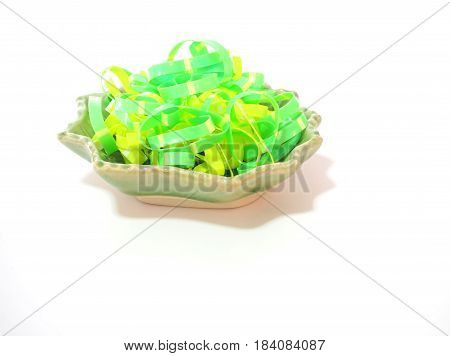 Colorful rubber band in a bowl on white background