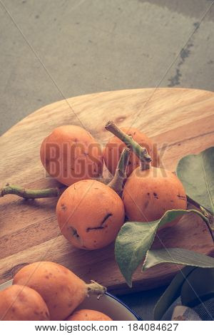 loquats on kitchen counter background. Vintage style.