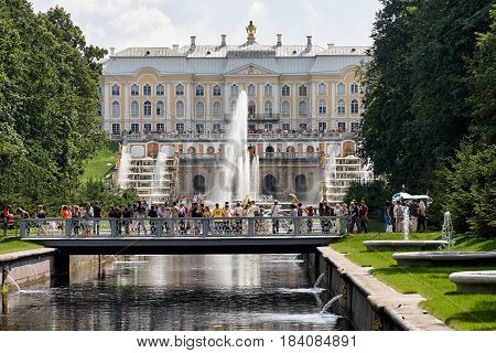Petergof, Saint-Petersburg, Russia - July 23, 2009: Many people near The Samson Fountain and The Grand Cascade in The Lower Park. On the background is The Grand Palace and The Armorial Pavilion