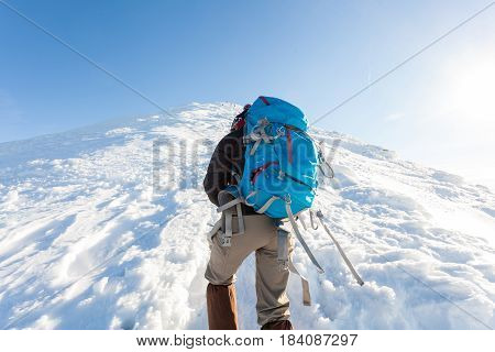 Male tourist with blue backpack rises in the snowy mountains. Ukrainian Carpathians in the winter