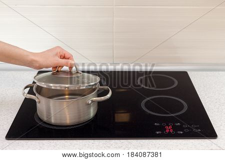 Woomen hand open a saucepan in modern kitchen with induction stove