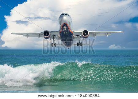 Passenger liner sets to land above the beach and turquoise waves of the Indian Ocean.