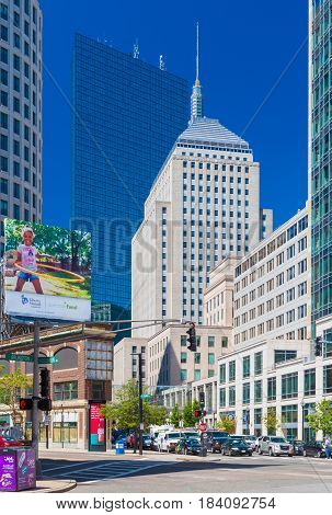 Boston - June 2016, USA: The street of Boston, view of John Hancock Tower, Berkeley Building and surrounding buildings in Back bay district, cars on intersection