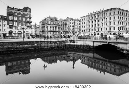 Trieste - December 2016, Italy: Old historical buildings mirror reflected in water, Grand Canal in Trieste city center, black and white cityscape