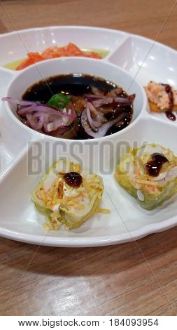 A round white plate with sushi and ceviche