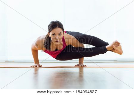 Portrait of beautiful young woman practicing acro yoga at home.