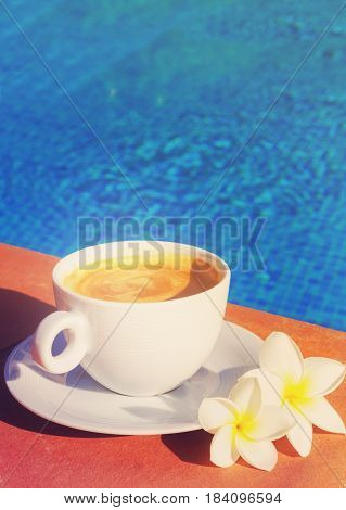 white cup of coffee near pool blue water with copy spacer, retro toned