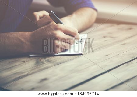man hand pen and notebook on wooden table