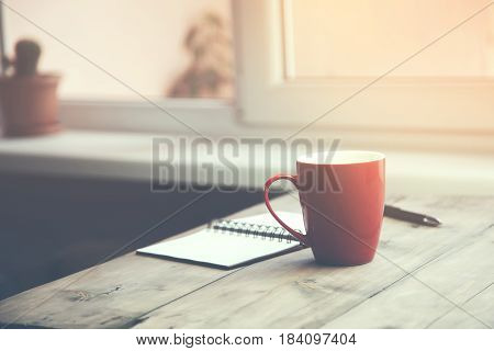 A cup of coffee with notebook and pen