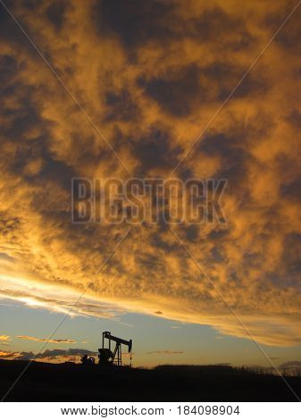 Single silhouetted oil pumper jack under an orange cloud