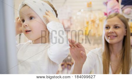 Baby's dress store - little blonde baby girl with mother doing shopping and buying pretty hat, telephoto